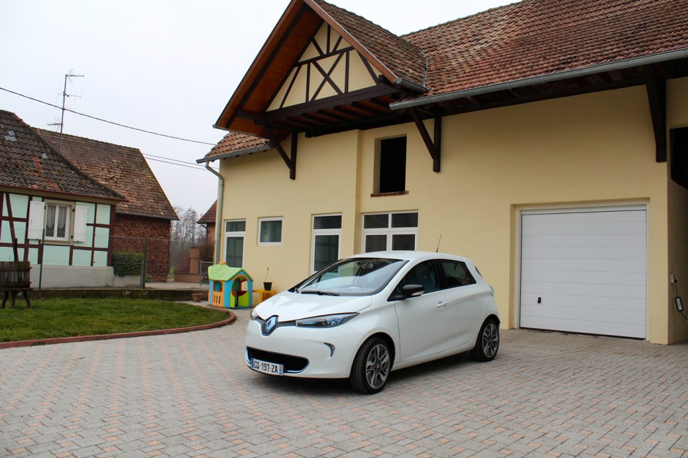 Three-quarters view of the Renault ZOE in front of the garage.